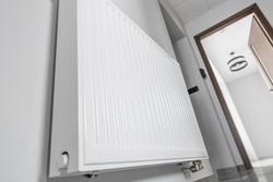 Residential Energy Saving Theme. White Modern Wall Mounted Central Heating Water Radiator in the Apartment.