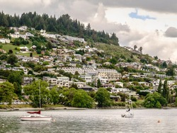 Residential hillside in Queenstown, New Zealand, with two sailboats moored in Lake Wakatipu