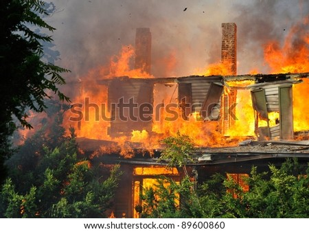 residential house in suburbs on fire, fully engulfed in flames