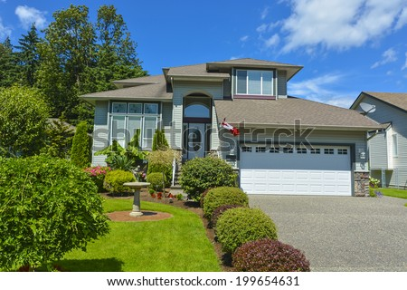 Residential house with garage on blue sky background.