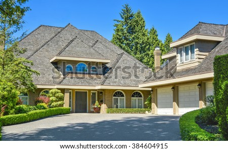 Residential house with massive roofs, green hedge in front on blue sky background. Family house with big roofs tiled by wooden shingles. House with detached garage for three parking lots.