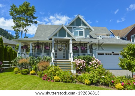 Residential house with patio and garage on blue sky background. Family house in British Columbia, Canada.