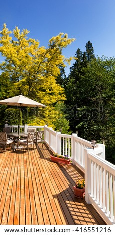 Residential outdoor cedar deck with furniture and umbrella during nice bright day. Vertical layout.  #416551216