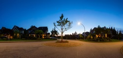 Residential Suburban Neighborhood in the City during a vibrant spring sunset. Taken in Fraser Heights, Surrey, Vancouver, BC, Canada. Panorama, Wide Angle