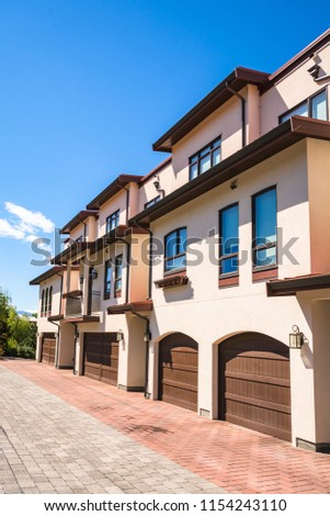 Residential townhouses with wide garage door. Residential townhouses on blue sky background on sunny day