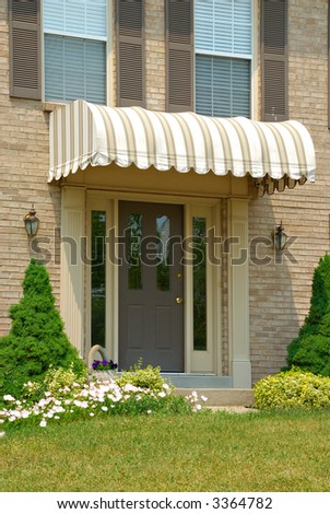 Residential two story brick home entryway in an upscale neighborhood.