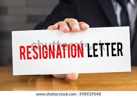 Resignation letter, message on white card and hold by businessman
