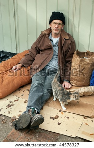 Resigned looking mature homeless man seated on the street with a friendly stray cat.