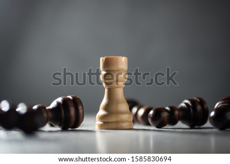 Resilience, perseverance and victory concept. Rook standing among fallen pawns.