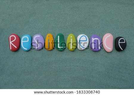 Resilience, the ability to be happy or successful again after something difficult or bad has happened. Creative handmade multicolored stone letters of resilience text over green sand