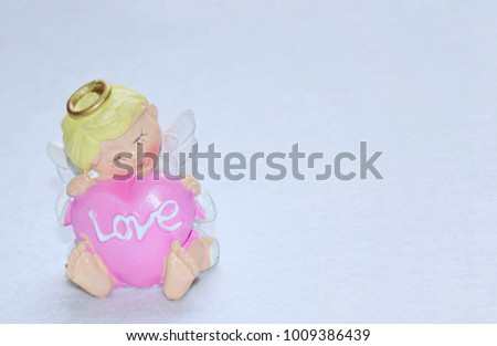 Resin angel doll hugging pink heart shape with Love text on white background, Love concept. #1009386439