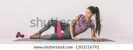 Resistance band clamshell exercise fit girl training legs on floor mat demonstration. Hip abductor workout for burning calories. #1303216792