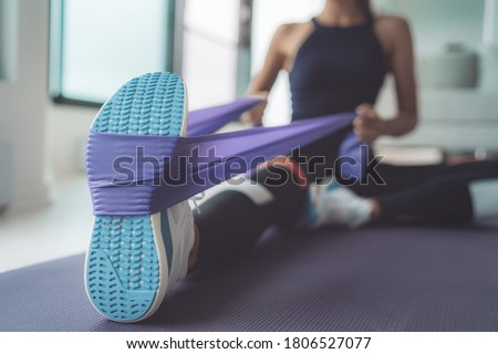 Resistance band exercise at home. Woman doing pilates workout using elastic strap pulling with arms for shoulder training on yoga mat indoors.