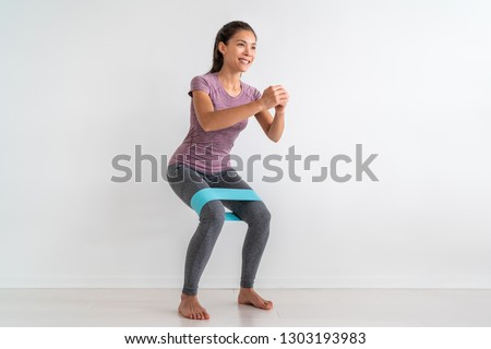 Resistance band exercises with fabric elastic equipment. Crab walk squat exercise fit Asian fitness woman training at home.