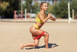 Resistance band fitness woman doing squat exercise for glutes on the beach. Athletic girl workout with fitness loop band outdoors