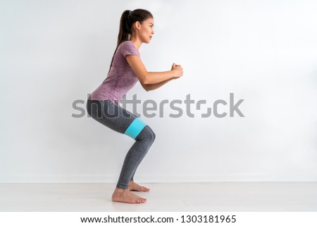 Resistance band fitness woman doing squat exercise with fabric booty band stretching strap. Crab walk squatting workout girl training at home. #1303181965