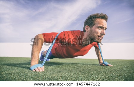 Resistance band pushup fit man fitness exercise with rubber bands as added difficulty. Push-ups exercising athlete.