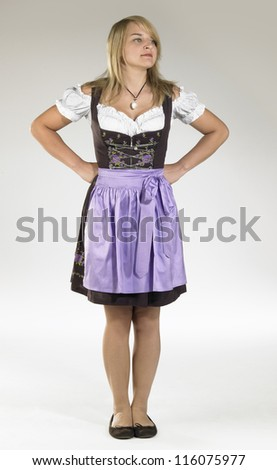 resolute blond woman wearing a traditional dress named dirndl - stock photo