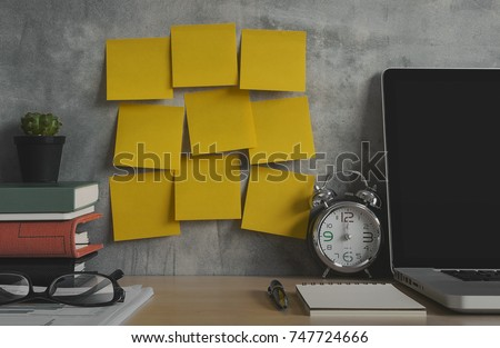 Resolutions, notes, goals, post, memo or action plan concept. Sticky notes on loft wall in workplace office with laptop, notebook, eye glasses, clock, plant, books and stationery on wooden desk.