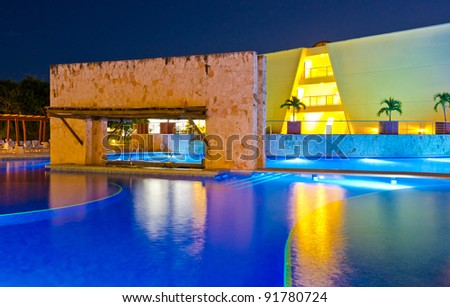 Resort building with the swimming pool at night time - stock photo
