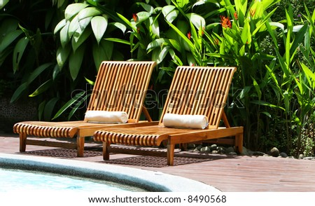 Resort lounge chairs surround an elegant pool