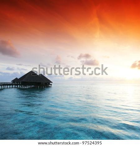 resort maldivian houses on sunrise