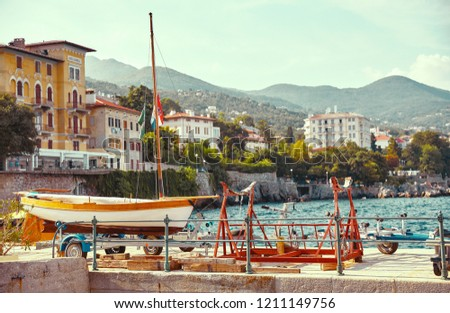 Resort town Lovran, Croatia. Boat at piers by sea near coast. Mountains far away and blue sky. Summer seaside Croatian landscape with sunny day.