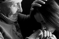 Respect for daughter to her grandmother. A young girl respects an old grandmother. Black and white closeup photo of an old grandmother and a young girl.