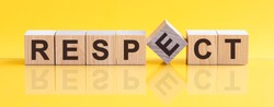 Respect word written on wood block. Respect word is made of wooden building blocks lying on the yellow table. Respect, business concept, yellow background