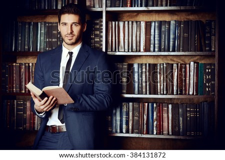 Respectable young man in the old library. Classic vintage interior.