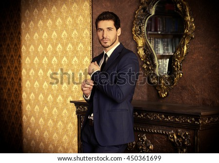 Respectable young man standing by a fireplace in a room with classic interior. Luxury. Men\'s beauty, fashion.