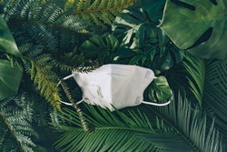 Respiratory or surgical face mask. Coronavirus or COVID-19 protection on tropical leaves background. Pandemic or epidemic concept.