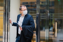 Respiratory protection, coronavirus, dangerous disease. Serious man stands in doors of office building, wears medical mask, holds modern cellphone, newspaper to read article about covid-19 treatment