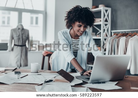 Shutterstock Responding on business e-mail. Beautiful young African woman working using computer and smiling while standing in workshop