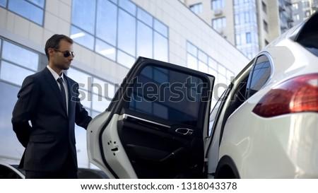 Responsible driver opening car door for his boss, luxury service, duties