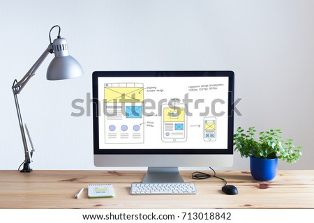 Responsive web design development technology concept with desktop computer in modern bright office and website wireframe sketch layout on screen, nobody