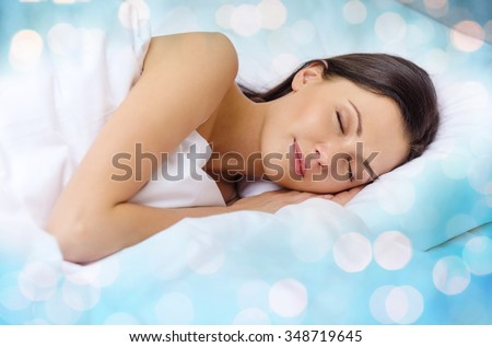 rest and comfort concept - beautiful woman sleeping in bed over blue lights background