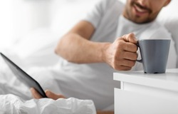 rest and people concept - close up of young man with tablet pc computer drinking coffee in bed at home in morning