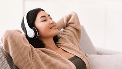 Rest And Relax Concept. Closeup portrait of calm asian woman lying on couch, listening to music, audio book, podcast, enjoying meditation for sleep and peaceful mind in wireless headphones, copy space