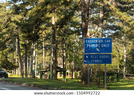 Rest area by highway road in Alabama with rest area sign, passenger car parking only and restrooms with telephone at visitor center in Lanett, Alabama #1504992722