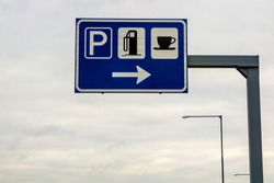 Rest area sign on a pole on freeway road. Signs for parking, gas petrol station and coffee food store.