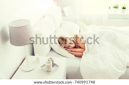 rest, comfort and people concept - young woman sleeping in bed at home bedroom