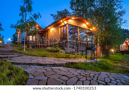 Rest in the cottages. Cottage village in the evening. Country houses with a barbecue area. Stay in the fresh air. Cottages in a beautiful location. Landscape design. Foto stock ©