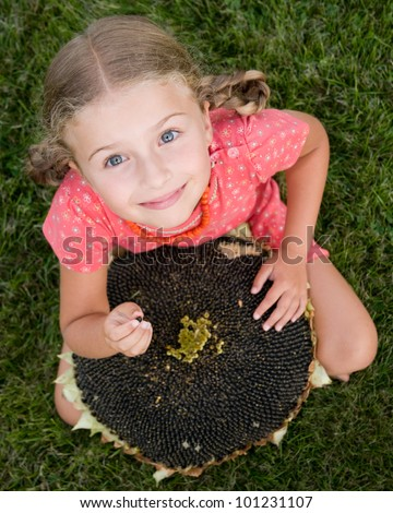 Rest in the garden - adorable girl with the seeds of the sunflower