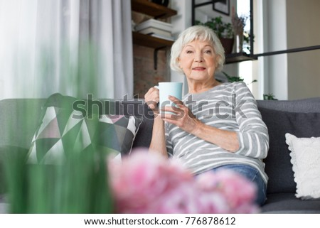 Rest moment. Waist up portrait of senior joyful woman looking at camera. She is holding hot drink and smiling while relaxing on comfortable couch #776878612