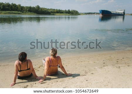 Rest on the river bank. Two girls sitting sunbathing on the riverbank and see a huge floating ship. Sunbathe on the beach. #1054672649