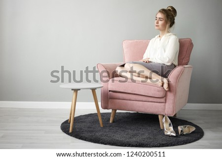 Rest, recreation, coziness and relaxation concept. Portrait of beautiful calm young businessman wearing white blouse and skirt relaxing in armchair and looking into distance, having peaceful look #1240200511
