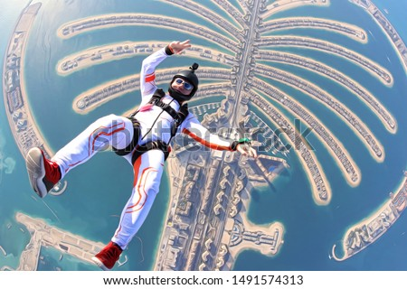 Rest. Tourism Sky diving crazy men rest on UAE Dubai sea palm in free fall. Goal skydive Dubai. Summer crazy jump.