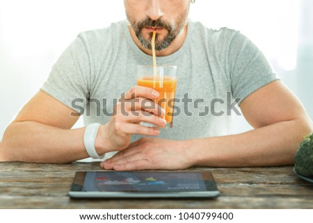 Rest with pleasure. Concentrated pleasant relaxed man sitting by the table looking at the laptop drinking juice. #1040799400