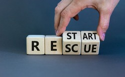 Restart and rescue symbol. Businessman turns cubes and changes the word 'restart' to 'rescue'. Beautiful grey background. Business and restart - rescue concept. Copy space.